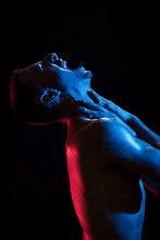 Side View Of Unhappy Shirtless Sporty Male Shouting With Eyes Closed While Embracing Himself With Arms Crossed On Chest And Neck In Light Of Red And Blue Lamps On Black Background