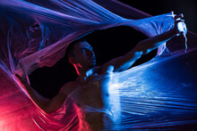 Aggressive Male In Casual Clothing Shouting And Looking At Camera While Ripping Transparent Tape In Light Of Red And Blue Lamps