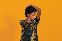 Young Contemplative African American Female In Trendy Wear With Afro Hairstyle Standing With Eyes Closed Standing On Studio With Orange Background