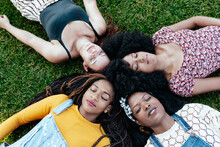Top View Of Delighted Multiracial Female Friends Relaxing On Green Lawn In Park And Closed Eyes While Enjoying Weekend Together