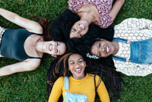 Top View Of Delighted Multiracial Female Friends Relaxing On Green Lawn In Park And Looking At Camera While Enjoying Weekend Together
