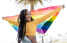 Low Angle Of Proud African American Female Standing With Fluttering LGBT Rainbow Flag On Street And Cheerfully Looking Away