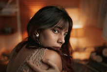 Back View Of Female In Lace Bra Embracing Herself While Sitting In Cozy Room Lit By Dim Orange Light Looking Over The Shoulder To The Camera