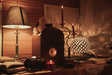 Burning Candles And Illuminated Old Fashioned Lamp Placed On Table With Vintage Clock In Cozy Room With Dim Light