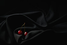 Red Small Cherries On Thin Stems Placed On Dark Black Wrinkled Cloth In Studio