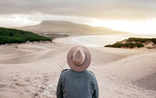 Back View Unrecognizable Male In Denim Jacket And Hat Standing On Sandy Beach And Admiring Picturesque Hilly Seacoast View