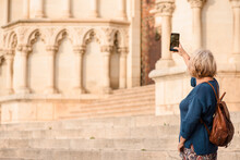 Side View Of Unrecognizable Female Traveler With Smartphone Standing On Steps And Taking Pictures Of Exterior Of Medieval Cathedral While Visiting Cuenca Town In Spain