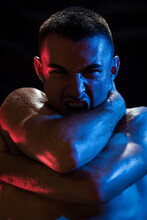 Unhappy Shirtless Sporty Male Shouting Looking At Camera While Embracing Himself With Arms Crossed On Chest And Neck In Light Of Red And Blue Lamps On Black Background