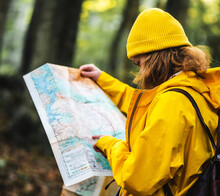 Side View Of Female Explorer In Yellow Raincoat And With Backpack Standing In Woods And Searching For Route On Paper Map