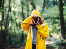 Unrecognizable Female Traveler In Yellow Raincoat And Hat Taking Picture On Photo Camera While Exploring Nature In Woods