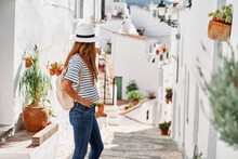 Happy Charming Female Tourist Wearing Stylish Sunhat Standing On Historic Street During Stroll In Frigiliana And Looking Away During Vacation