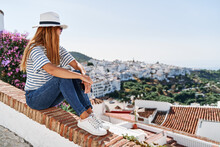 Side View Of Female Tourist In Sunhat And Casual Wear Sitting On Stone Border And Enjoying Cityscape Of Frigiliana While Embracing Knees And Looking Away