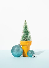 Artificial Spruce Branches Decorated With Silver Christmas Baubles Placed In Ice Cream Cup On Table In Studio On Blue Background