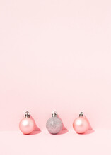Decorative Christmas Baubles Arranged On Pink Background In Studio For Holiday Celebration