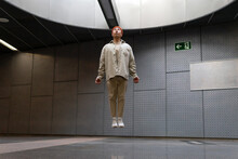 Full Body Focused Stylist Asian Male Wearing Casual Outfit Levitating With Eyes Closed Above Floor In Building Hallway