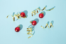 Shiny Christmas Baubles Placed On Blue Background In Studio