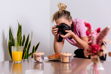 Professional Female Photographer Taking Picture Of Desserts And Glass Of Orange Juice While Working Remotely From Home