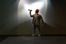 Full Body Overwhelmed Male In Casual Clothes Screaming In Loudspeaker While Standing Against Gray Wall In Dark Room
