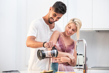 Loving Couple In Pajamas Hugging And Pouring Fresh Coffee In Cup Together While Standing At Table In Kitchen During Breakfast In Morning
