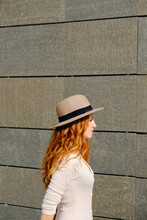 Side View Of Attractive Young Female With Long Red Hair Wearing Stylish Hat Looking Away While Standing Near Stone Urban Building