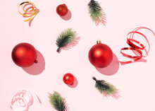 From Above Of Red Christmas Balls And Green Spruce Branches Arranged With Shiny Ribbons On Pink Background In Studio
