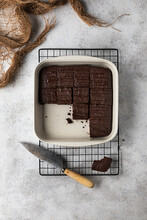 Top View Of Ceramic Baking Pan With Traditional Brownie Cake Cut Into Pieces Placed On Metal Grid With Knife On Kitchen Table