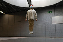 Full Body Focused Asian Male Wearing Casual Outfit And Face Mask Levitating With Eyes Closed Above Floor In Building Hallway