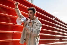 Agitating Asian Male Screaming In Megaphone While Standing With Fist Up Near Red Metal Fence And Looking Away In Rage