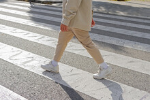 Cropped Unrecognizable Male Pedestrian Wearing Casual Outfit Crossing On Zebra Crosswalk On The Street On Sunny Day