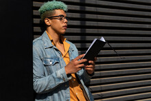 Black Male Hipster Standing On Street And Enjoying Interesting Story In Book While Entertaining At Weekend In City