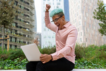 Side View Low Angle Of Excited African American Male Entrepreneur Rejoicing At Success In Project While Sitting With Laptop And Raised Fist On Street