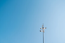 Low Angle Of Modern Surveillance Cameras Mounted On Metal Pole In City On Background Of Blue Cloudless Sky