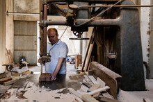 Serious Male Carpenter Using Band Saw And Cutting Wooden Plank At Workbench In Messy Workshop