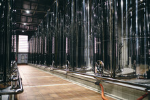 Rows Of Shiny Stainless Steel Reservoirs Placed In Bright Industrial Area Of Modern Factory