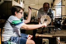 Focused Teenage Boy Working With Old Drill Press Under Supervision Of Father While Polishing Detail In Workshop