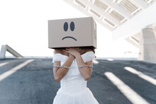 Anonymous Female In White Bridal Dress With Metal Chain Tying Arms Wearing Cardboard Box With Unhappy Smiley