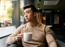 Thoughtful Asian Male Relaxing In Armchair In Cozy Coffee Shop And Enjoying Hot Beverage While Looking Away
