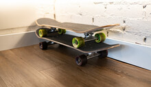 Sport Equipment For Skateboarding Placed Near White Brick Wall In Corner Of Room