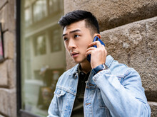 Serious Young Asian Male In Casual Outfit Speaking On Mobile Phone While Standing Near Stone Wall Of Urban Building