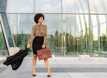 Full Body Of Cheerful Stylish African American Female Employee With Afro Hair And Briefcase Holding Jacket In Hands Standing Near Glass Walled Building