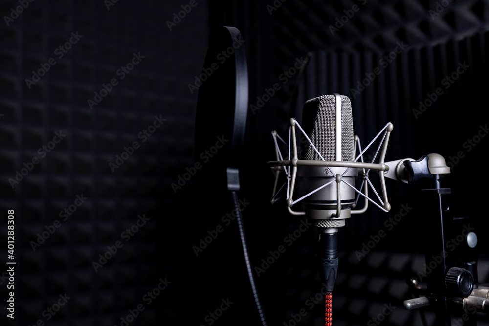 Contemporary metal microphone with wire placed on background of soundproof foam with pyramid shaped pattern in dark music recording studio