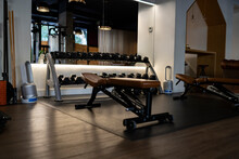 Interior Of Modern Gym With Equipment And Kettlebells Placed Near Mirror With Press Benches