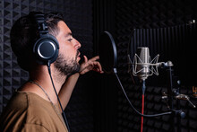 Side View Of Male Singer In Headphones Standing In Acoustic Room With Soundproof Walls And Microphone And Recording Song In Studio