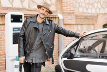 Trendy Happy Brutal Male In Hat Standing Near Contemporary Electric Automobile On Charge Station Near Brick Stone Wall