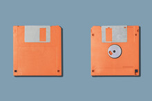 Top View Of Old Fashioned Orange Magnetic Floppy Disks For Computer Placed On Gray Background