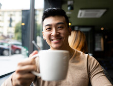 Asian Male Relaxing In Armchair In Cozy Coffee Shop And Enjoying Hot Beverage While Looking At Camera
