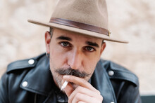 Cool Handsome Guy In With Gorgeous Mustache Smoking Cigarettes And Looking At Camera On Blurred Background