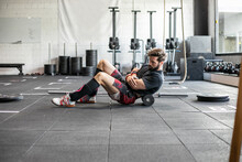 Side View Of Male Weightlifter Doing Abdominal Crunches While Training In Bright Gym