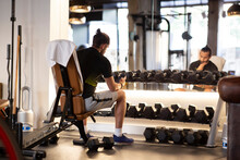 Back View Of Adult Sportsman Sitting On Bench And Browsing Smartphone During Break In Contemporary Gym