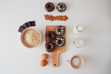 Top View Composition With Sweet Donuts With Chocolate Topping And Sprinkles Placed On Wooden Board On White Table With Ingredients For Recipe